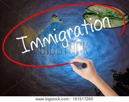 Woman Hand Writing Immigration With Marker Over Transparent Board