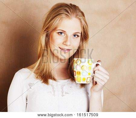 young cute blond caucasian girl drinking coffee close up on warm brown background