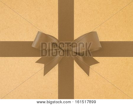 dark brown ribbon with bow on brown paper texture background, simple decoration gift box earth tone color