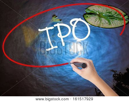 Woman Hand Writing Ipo (initial Public Offering)   With Marker Over Transparent Board