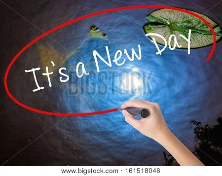 Woman Hand Writing It's A New Day With Marker Over Transparent Board