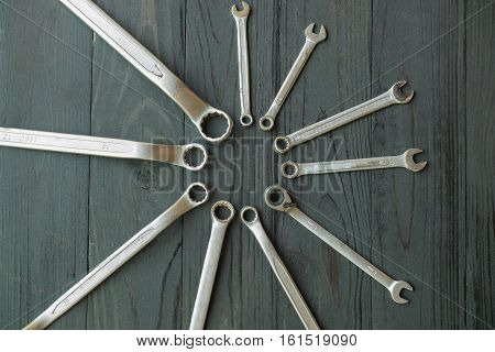 Many fix wrenches on black wooden placed in a circle.
