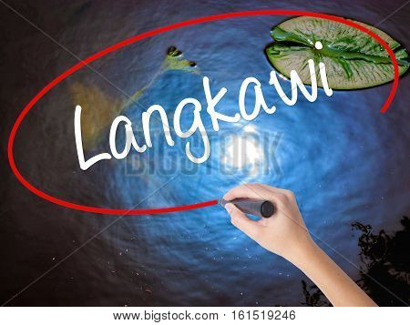 Woman Hand Writing Langkawi  With Marker Over Transparent Board.