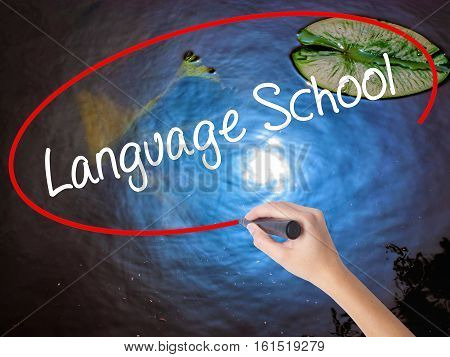 Woman Hand Writing Language School With Marker Over Transparent Board