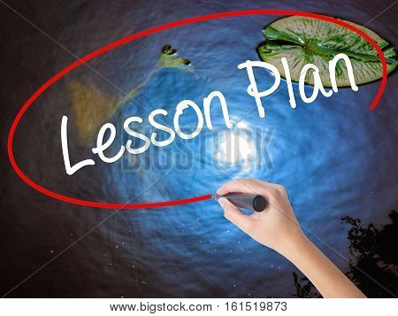 Woman Hand Writing Lesson Plan With Marker Over Transparent Board
