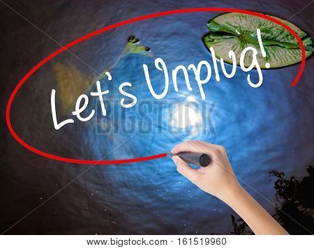 Woman Hand Writing Let's Unplug! With Marker Over Transparent Board