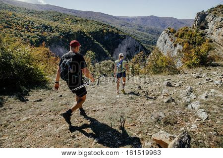 man and woman with walking poles and backpacks go on a mountain trail