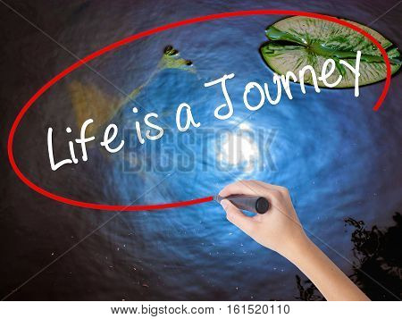 Woman Hand Writing Life Is A Journey With Marker Over Transparent Board.