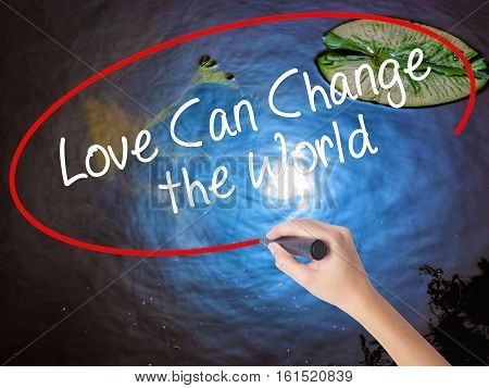 Woman Hand Writing Love Can Change The World With Marker Over Transparent Board