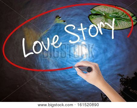 Woman Hand Writing Love Story With Marker Over Transparent Board