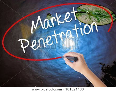 Woman Hand Writing Market Penetration With Marker Over Transparent Board