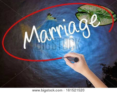 Woman Hand Writing Marriage With Marker Over Transparent Board