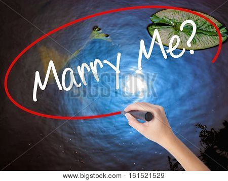 Woman Hand Writing Marry Me? With Marker Over Transparent Board.