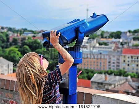 Little traveler trying to use coin-operated binoculars to see the city skyline