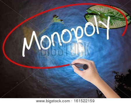 Woman Hand Writing Monopoly With Marker Over Transparent Board.