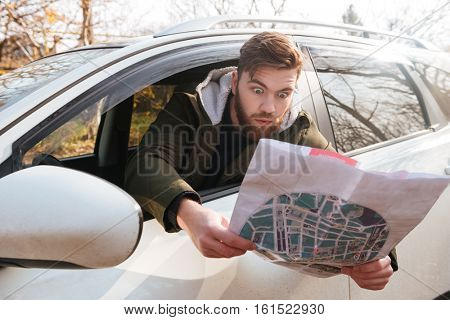 Image of losted in the forest bearded shocked driver sitting in car while holding map. Looking at map.