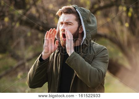 Image of losted in forest bearded man standing and calling to the aid. Looking aside.