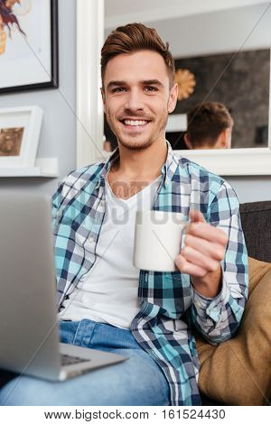 Picture of cheerful bristle man dressed in shirt in a cage print sitting on sofa in home and using laptop computer. Looking at camera while drinking tea.