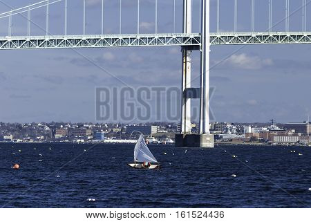 Jamestown Rhode Island USA - January 13 2008: Small sailboat cuts across Narragansett Bay near Newport Bridge
