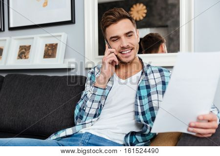Photo of handsome young bristle man dressed in shirt in a cage print sitting on sofa in home and talking by phone while looking at documents.