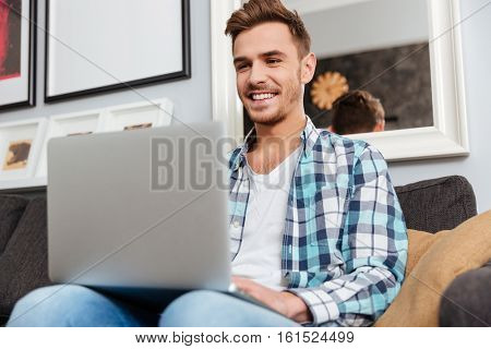 Photo of happy bristle man dressed in shirt in a cage print sitting on sofa in home and using laptop computer. Looking at laptop computer.