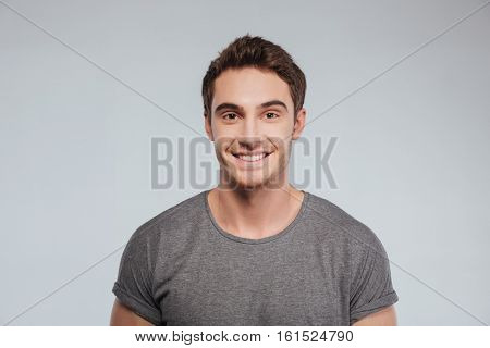 Portrait of an attractive smiling man in t-shirt looking at camera over white background
