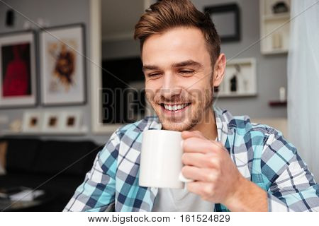 Happy young bristle man dressed in shirt in a cage print sitting in home and holding cup of tea.