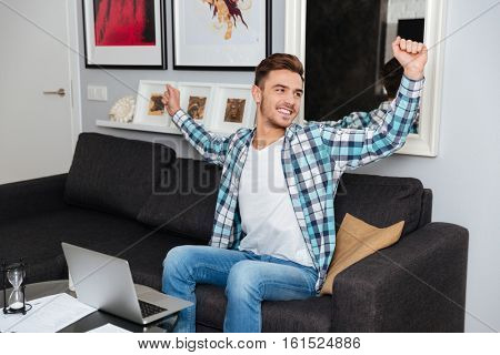 Photo of cheerful bristle man dressed in shirt in a cage print sitting on sofa in home and using laptop computer while stretching.