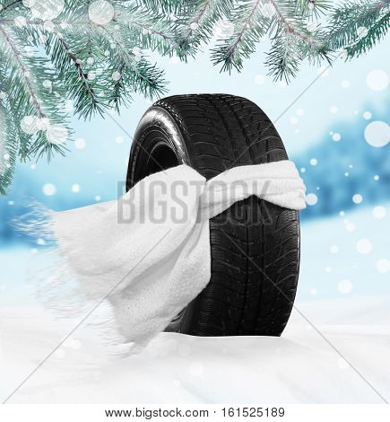 Car tire in scarf on snow against nature background. Winter tires concept.