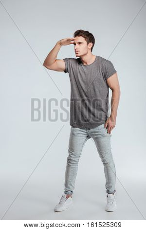 Full length portrait of a serious young man straring and looking far away over white background