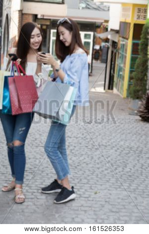 Happy Asian Woman With Smartphone And Colorful Shopping Bags At Department Store Shopping Mall, Blur