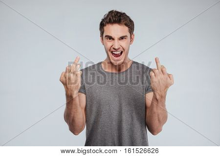 Portrait of a young man showing middle finger gesturing fuck isolated on white background