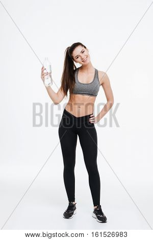 Full length portrait of a smiling cheerful fitness woman standing and holding water bottle isolated on a white background
