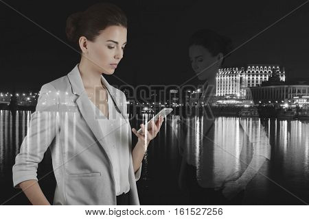 Double exposure of woman with phone and night cityscape background. Business concept. Black and white photo.
