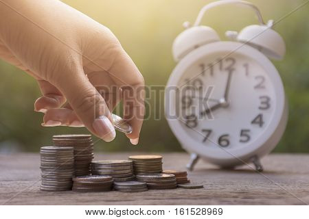 Women Hand Stacking Gold Coins With Wooden Background And Clock .business Finance And Money Concept,