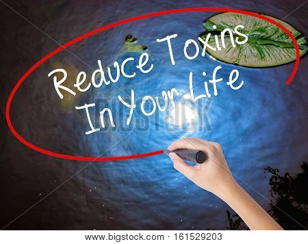 Woman Hand Writing Reduce Toxins In Your Life With Marker Over Transparent Board