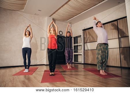 a group of people performs a back bend, exersice in yoga