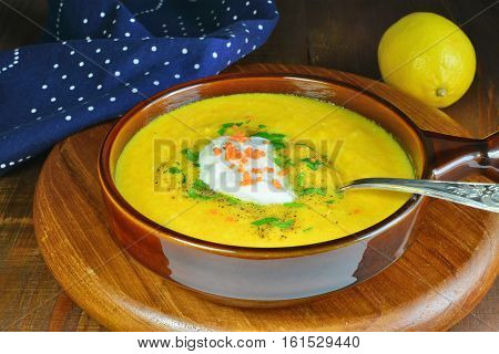 Carrot cream soup with sour cream and fresh herbs in a brown stoneware bowl over wooden table