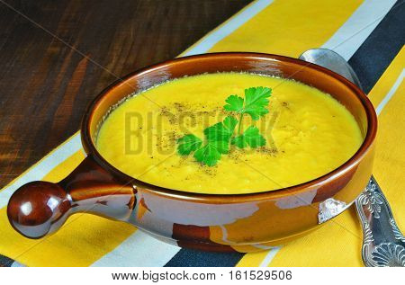 Pumpkin and carrot soup with parsley in a brown stoneware bowl seasoned with parsley and ground black pepper