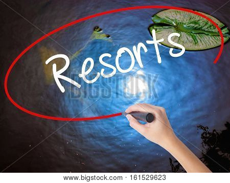 Woman Hand Writing Resorts  With Marker Over Transparent Board