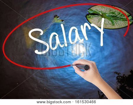 Woman Hand Writing Salary  With Marker Over Transparent Board