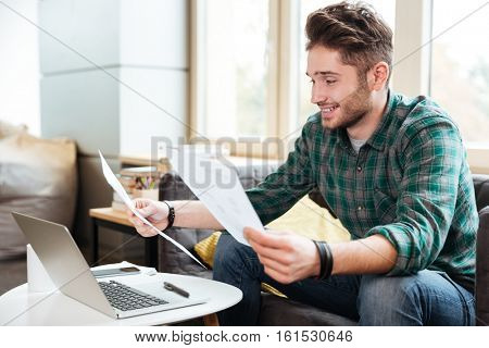 Man with documents sitting on sofa by the table with laptop. Side view. Coworking