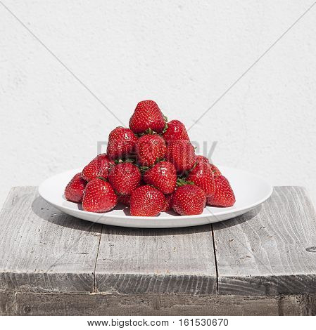 Ripe red strawberries forming a pyramid on a plate, wit natural lighting