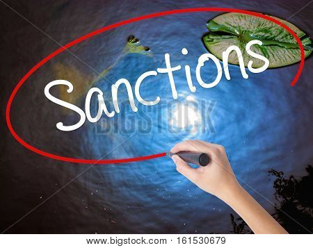Woman Hand Writing Sanctions With Marker Over Transparent Board.