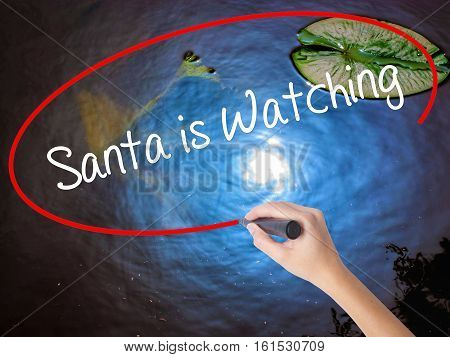 Woman Hand Writing Santa Is Watching With Marker Over Transparent Board