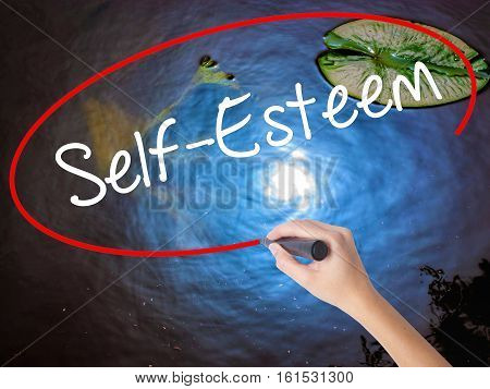 Woman Hand Writing Self-esteem With Marker Over Transparent Board.