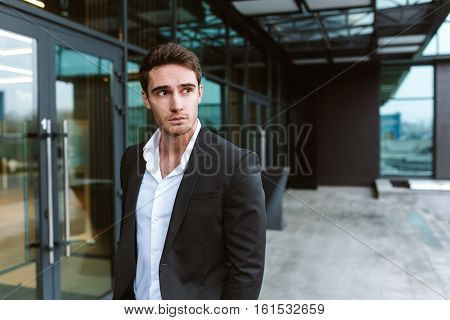 Serious business man in suit standing near the office and looking away