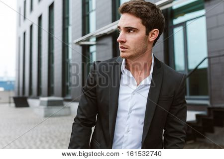 Surious business man in suit standing outdoors and looking aside