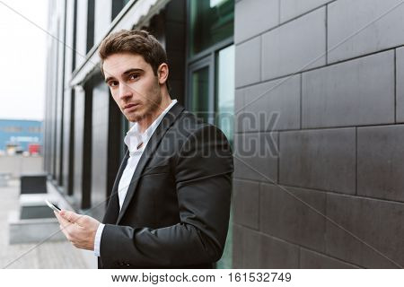 Side view of business man in suit standing outdoors with phone near the office and looking at camera
