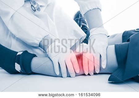 Youth Soccer Player Knee Pain, On White Background. Doctor Perform Checking At Knee Patient.